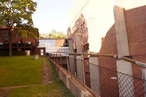 Gräs och träd till vänster i bild. Byggnad till höger.